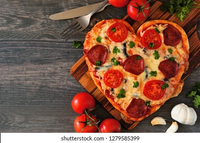 Heart shaped pizza for Valentines Day over a dark wood background. Top view, side orientation. Table scene with ingredients.