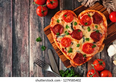 Heart shaped pizza for Valentines Day over a dark wood background. Top view, side border. Table scene with ingredients.