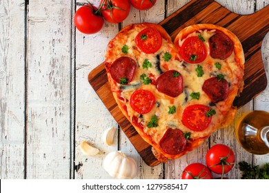 Heart shaped pizza for Valentines Day over a white wood background. Top view, side border. Table scene with ingredients.