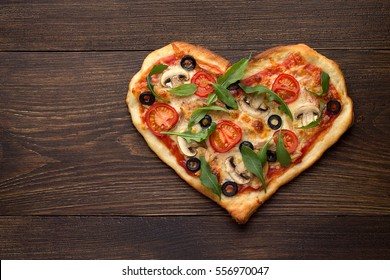 Heart shaped pizza for Valentines day on dark rustic wooden background with text love. Top view, copy space.