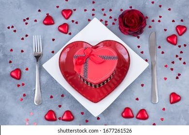 heart shaped plate, cutlery, gift in a box and festive decor