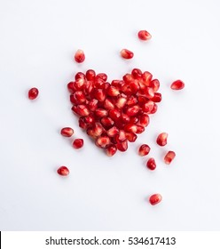 Heart shaped pomegranate seeds on white background. Love and Valentines day flat lay concept