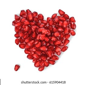 Heart shaped pomegranate seeds on white background. Love and Valentines day flat lay concept, top view