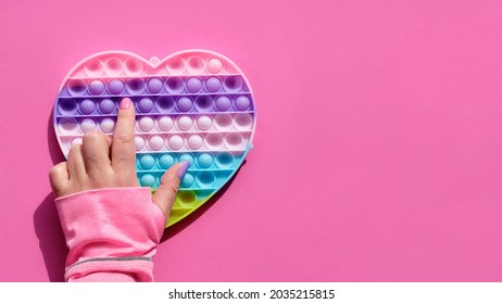 Heart shaped pope it antistress toy with female hand. Sensory simple dimple fidget in colors of LGBT. Flat lay on pink paper with copy-space. Aid for development of motor skills in fingers.