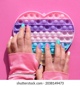 Heart shaped pope it antistress toy with female hand. Sensory simple dimple fidget in colors of LGBT. Flat lay on pink paper, square composition. Aid for development of motor skills in fingers.