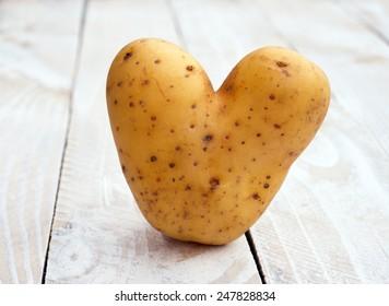 Heart shaped Potato - closeup image on wooden white background
