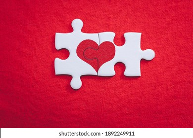Heart shaped puzzle pieces love valentine concept for valentines day and sweetest day on red gift box background