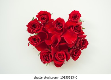 Heart shaped red roses and petals