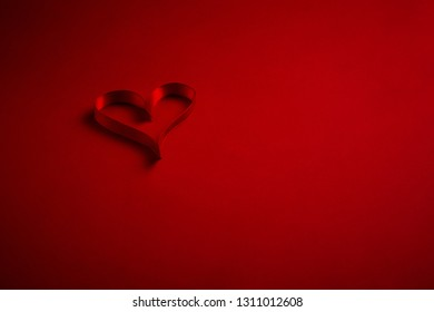 Heart shaped ribbon on plain background Valentines day romance concept