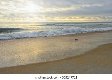 Heart shaped rock on beautiful sandy beach, cloudy sky, sun rays, reflections, and rolling waves in the blue hour just after sunrise, Palm Coast, Florida, USA in autumn.