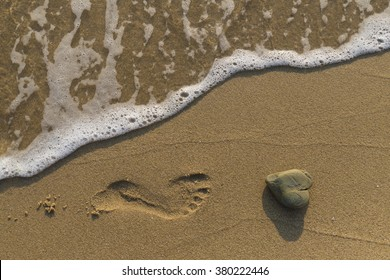 Heart shaped rock washed by the sea on a sandy beach.
