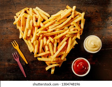 Heart shaped serving of French Fries with dips, dressings or sauce in small bowls alongside on wood