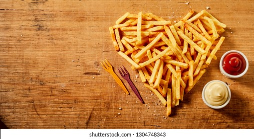 Heart shaped serving or fried potato chips, pommes frites or French fries on rustic wood with bowls of mustard and mayonnaise mix and tomato sauce viewed from overhead with copy space