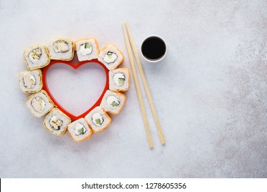 Heart shaped set of sushi rolls for Valentine's Day. Menu or delivery concept with space for text. Top view.