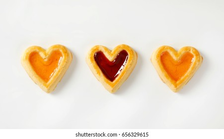Heart shaped shortbread cookies with apricot and cherry jam filling
