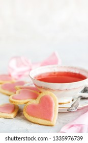 Heart shaped shortbread cookies and cup of red tea, Valentine concept, soft focus