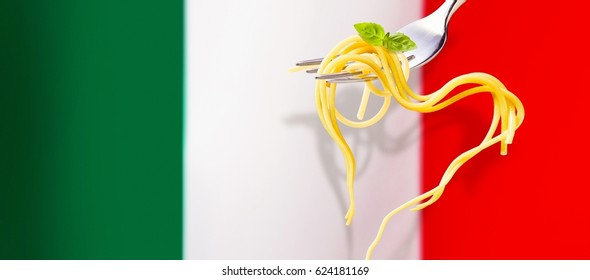 Heart shaped spaghetti garnished with fresh basil hanging from a silver fork over the Italian flag with copy space alongside in a panoramic banner