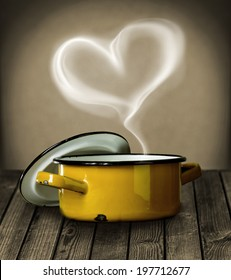 Heart shaped steam hovering in the air above a yellow enameled metal cooking pot symbolic of love on a rustic wooden kitchen counter