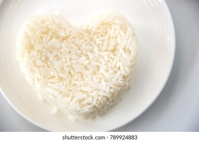 Heart shaped steamed rice on white plate