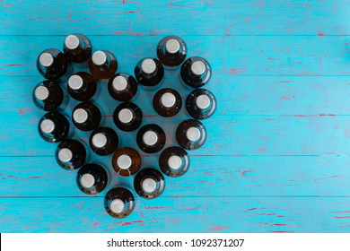 Heart shaped still life of capped beer bottles viewed top down on a blue picnic table conceptual of I Love Beer and summer parties with copy space