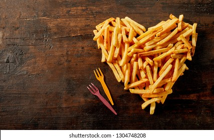 Heart shaped still life of French fries, pommes frites or potato chips viewed from above on vintage wood with copy space and plastic forks