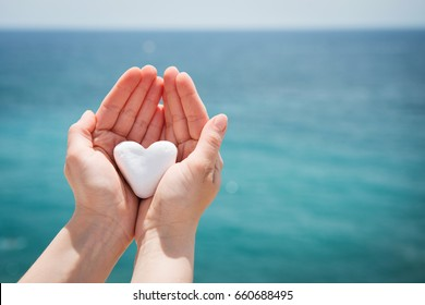 Heart shaped stone held in hands, sea in background