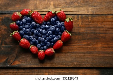 Heart shaped strawberries and blueberries on wooden background