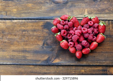 Heart shaped strawberries and raspberries on wooden background