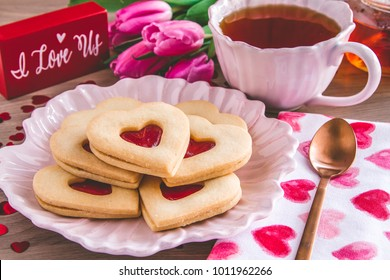 Heart shaped strawberry jam filled cookies sitting on pink plate with hot tea and pink tulips