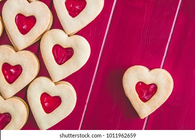 Heart shaped strawberry jam filled cookies on red wooden background with blank space