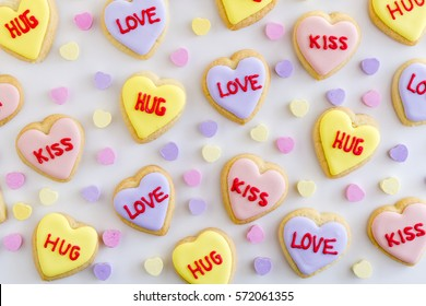 Heart shaped sugar cookies with colorful frosting and hand written messages with candy hearts on white background