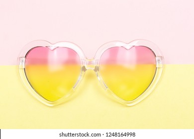 0a6ad42792e1 Heart shaped sunglasses with gradient lenses. Pastel pink and yellow color  block background