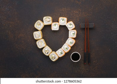Heart shaped sushi rolls with chopsticks and soy sauce for Valentine's Day.
