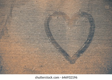 Heart shaped symbol on dusty wooden floor.