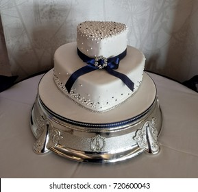 Heart shaped two tiered wedding cake on silver cake base