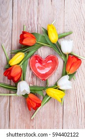 Heart shaped valentine gift with bunch of tulips on wooden background