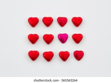Heart shaped, Valentine's Day chocolates on an isolated white background. A view from above looking down.chicolates lined up in rows and grid pattern.