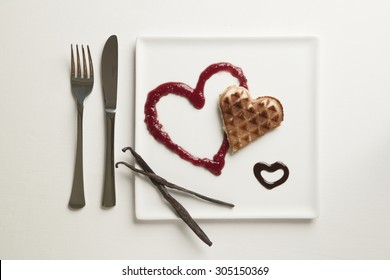 A heart shaped waffle on a heart shaped berry sauce and a chocolate sauce heart on a square plate garnished with vanilla pods on a white background, knife and fork