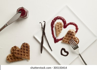 A heart shaped waffle on heart shaped berry sauce and chocolate sauce heart on square plate garnished with vanilla pod on white background, knife and fork, jam, two heart shaped waffles by the side