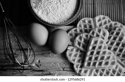 Heart shaped waffles with flour, eggs, cutting board, and whisk in black and white, monochrome.