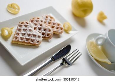 Heart shaped waffles with lemon zest, garnished with powdered sugar, served on rectangular plate on white table cloth, cup of tea with lemon in the background. Selective focus.