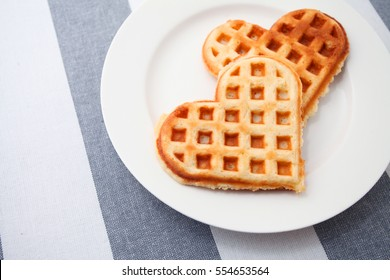 Heart shaped waffles on the modern stripped tablecloth background