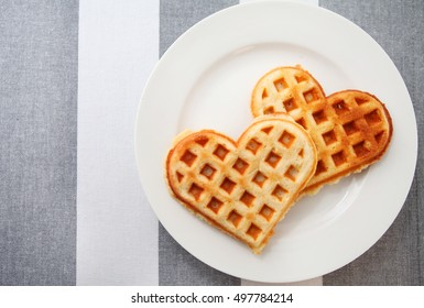 Heart shaped waffles over modern stripped tablecloth background