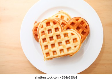 Heart shaped waffles over wooden table background