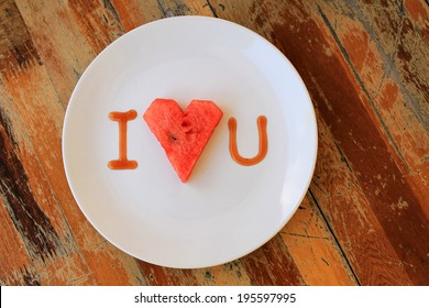 heart shaped watermelon in white dish on wood table