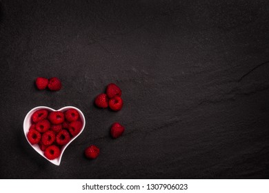 A heart shaped white bowl full of fresh organic raspberries on a dark rock background with copy space