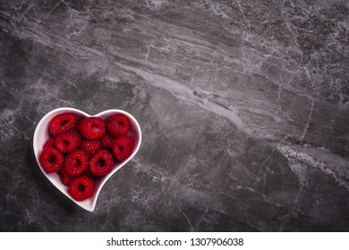 A heart shaped white bowl full of fresh organic raspberries on a marble stone background with copy space
