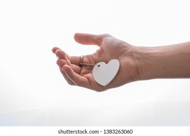 Heart shaped white object in hand on white background