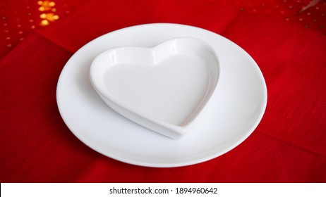 Heart shaped white plate on red background