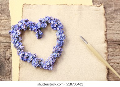Heart shaped wreath made of forget-me-not flowers. Vintage sheets of paper, copy space.